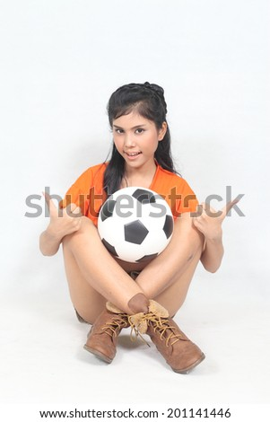 Portrait Beautiful woman hold ball over her head with wearing football top - stock photo