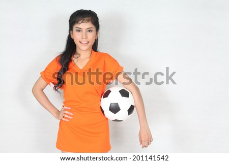 Portrait Beautiful woman hold ball with wearing football top  - stock photo