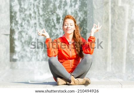 Portrait beautiful woman meditating yoga in lotus position isolated outdoors park waterfall background. Urban life style, stress relief techniques. Positive facial expression, emotion, life perception - stock photo