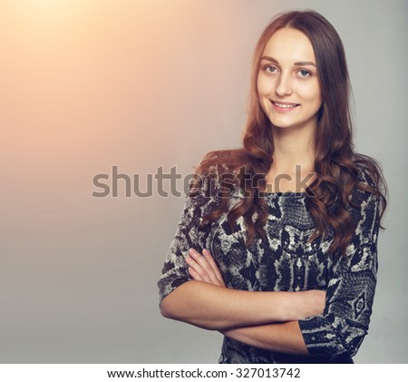 Portrait beautiful woman, of teen girl cheerful enjoying with long brunet hair and clean skin on gray background and orange light. Advertising concept about joy and happiness.