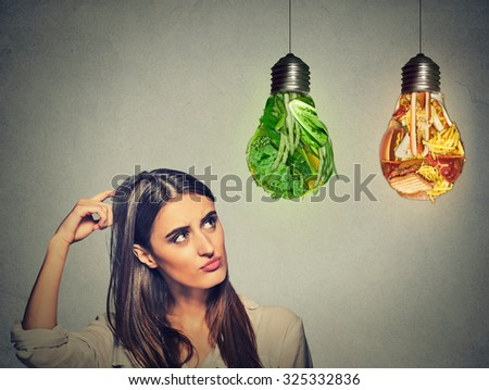 Portrait beautiful woman thinking looking up at junk food and green vegetables shaped as light bulb isolated on gray background. Diet choice right nutrition healthy lifestyle concept   - stock photo