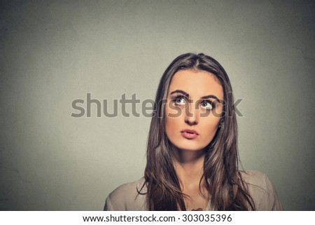 Portrait beautiful woman thinking looking up isolated on gray wall background with copy space. Human face expressions, emotions, feelings, body language, perception - stock photo