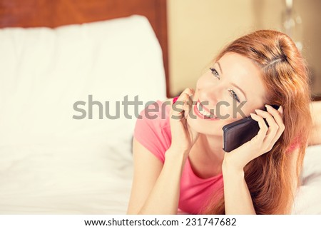 Portrait beautiful young happy woman using mobile phone lying in bed in a hotel room. Positive face expression emotion feeling. Communication, room service, travel concept  - stock photo