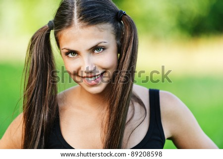portrait beautiful young woman smiling hair two long tail background summer green park