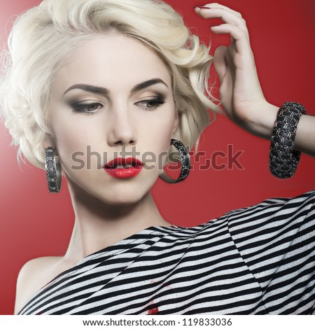 portrait beautyful young woman. in studio. red lips, red background and  jewelry - stock photo