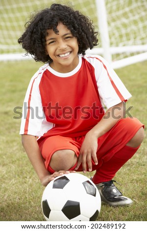 Portrait boy in soccer kit with ball - stock photo