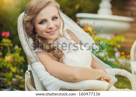 portrait bride in a wedding dress sits at chair - stock photo