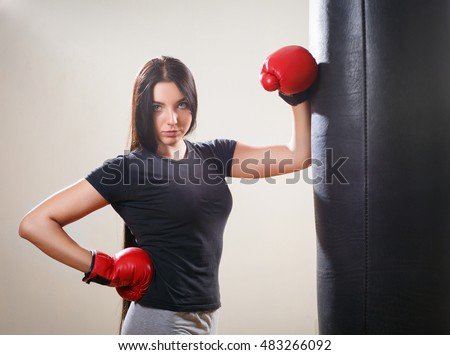Portrait brunette boxing girl in gloves and punching bag