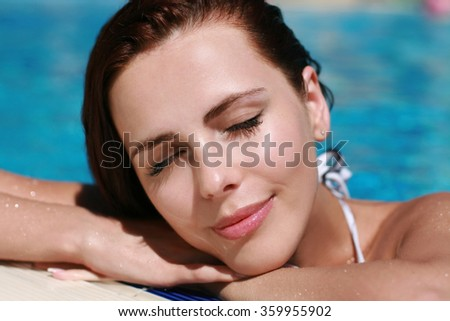 Portrait brunette with eyes closed in pool
