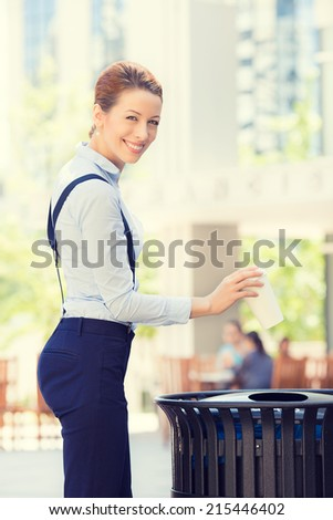 Portrait business woman throwing empty paper coffee cup in recycling bin, isolated outside sunny day, city background. Recycling, eco friendly approach concept. Keep streets, your town, earth clean - stock photo