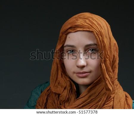 portrait cancer survivor girl in silk scarf on grey background - stock photo