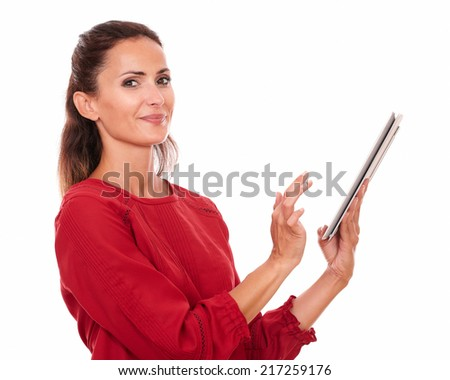 Portrait charming hispanic woman on red shirt using her tablet pc while smiling at you on isolated studio - stock photo