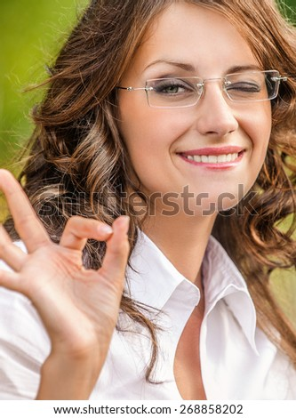 portrait charming young woman glasses shows sign good background road park - stock photo