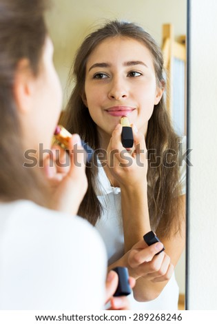 Portrait cheerful young girl admiring himself in front of the mirror - stock photo