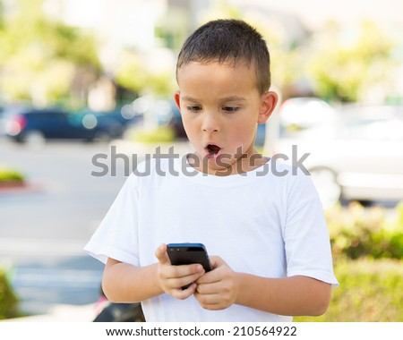 Portrait child, surprised boy, little man texting on mobile using smart phone isolated outdoor, outside background. Funny looking human face expression, emotion, reaction, body language. Communication - stock photo