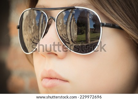 Portrait close up of a beautiful girl looking at the ruins of an ancient city with reflection of it in her sunglasses. Pompeii. Italy - stock photo