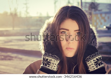 Portrait close up  of a teenage girl outdoor wearing gloves and winter coat with the faux - fur hood on. Toned effect