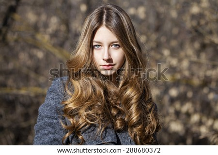 Portrait close up of young beautiful blonde schoolgirl on spring street background - stock photo