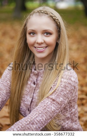 Portrait close up of young beautiful blonde women, on golden background autumn nature - stock photo