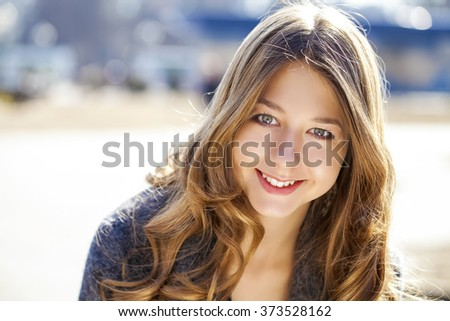 Portrait close up of young beautiful girl, on background spring street - stock photo