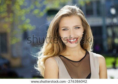 Portrait close up of young beautiful woman, on background summer street - stock photo