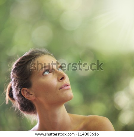 Portrait close up of young beautiful woman, on green background. Looking up - stock photo