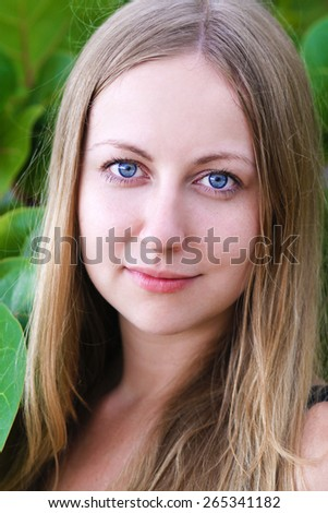 Portrait close up of young beautiful woman, on green background summer nature - stock photo