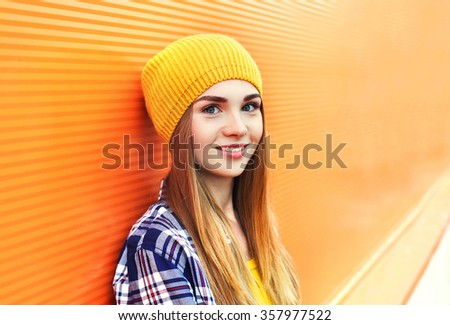 Portrait closeup beautiful young girl in yellow hat over colorful background - stock photo