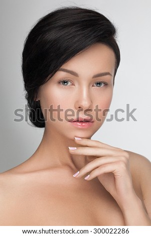 Portrait closeup of a young sensual attractive model woman looking at camera with great black long hair and magic hairstyle, nude daily fresh and pure makeup, french moon manicure. - stock photo