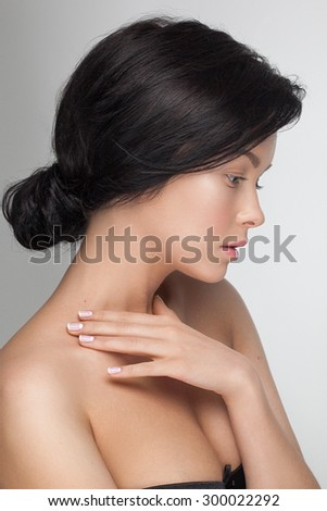 Portrait closeup of a young sensual attractive model woman looking down with great black long hair and magic hairstyle, nude daily fresh and pure makeup, french moon manicure. - stock photo
