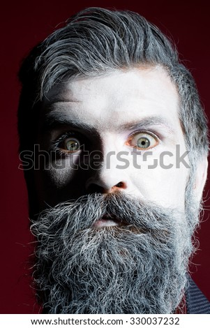 Portrait closeup view of one halloween holiday celebration character emotional man with spooky painted face of zombi and long white lush beard looking forward on purple background, vertical picture