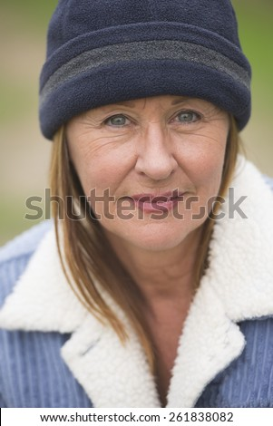 Portrait confident attractive mature woman outdoor, wearing warm blue bonnet and wool jacket, blurred green background. - stock photo