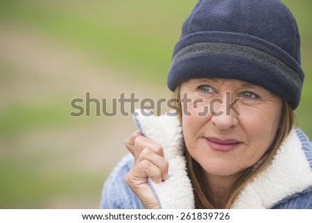Portrait confident attractive mature woman outdoor, wearing warm bonnet and wool jacket, blurred green background, copy space. - stock photo