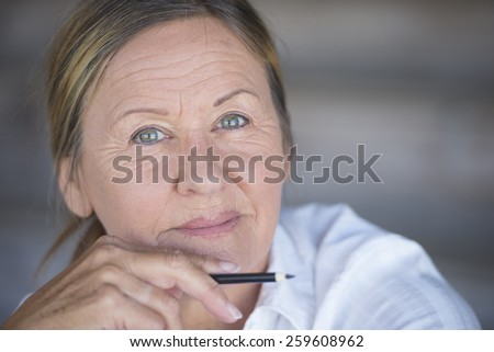 Portrait confident creative attractive mature business woman, thoughtful relaxed smiling, with pen in hand, blurred background, copy space. - stock photo