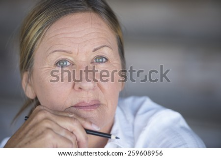 Portrait confident creative attractive mature business woman, thoughtful, serious, with pen in hand, blurred background, copy space. - stock photo