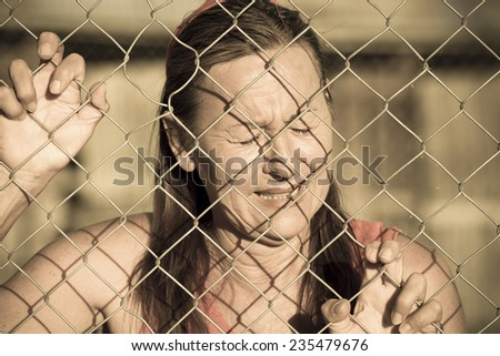 Portrait crying woman behind mesh wire fence, desperate, depressed, stressed facial expression, unhappy, closed eyes. - stock photo