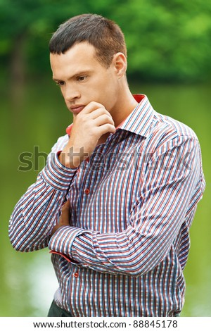 portrait cute young thoughtful man stands against background summer green park lake - stock photo