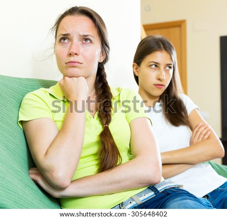 portrait depressed young women looking away after conflict at home - stock photo
