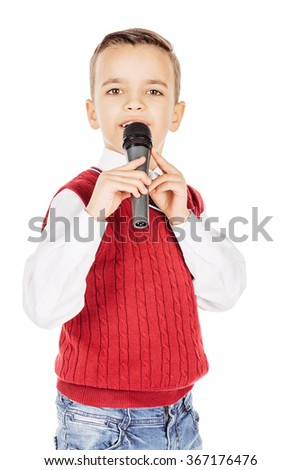 Portrait elegant young handsome joyful little kid singing on a black microphone isolated on white background.