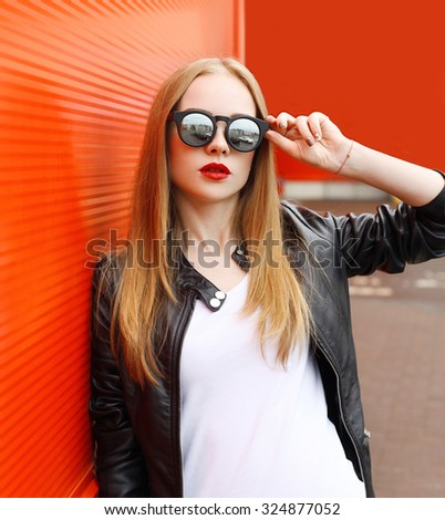 Portrait fashion pretty woman wearing a rock black leather jacket and sunglasses in city over red background - stock photo