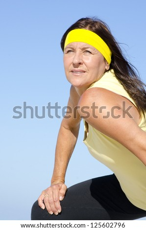 Portrait fit and healthy, confident and determined attractive looking mature woman exercising, isolated with blue sky as background and copy space. - stock photo