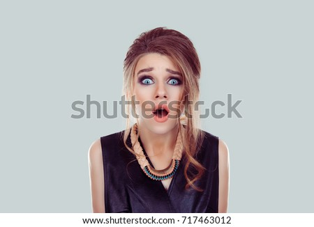 Portrait frightened shocked scared woman looking at camera isolated on light blue green white wall background. Human emotion facial expression body language unexpected reaction