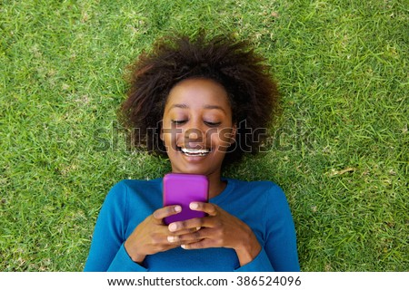 Portrait from above of a smiling african woman lying on grass looking at cell phone - stock photo