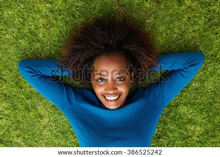 Portrait from above of a smiling black woman lying on grass - stock photo