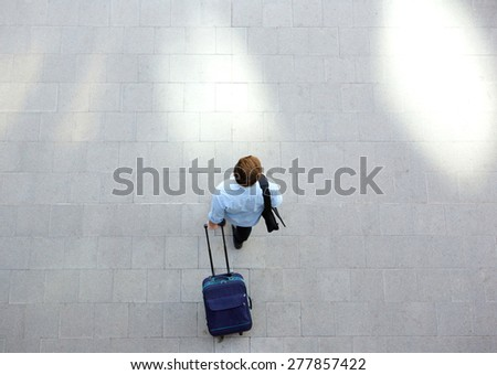 Portrait from above of a young man walking with luggage at station - stock photo