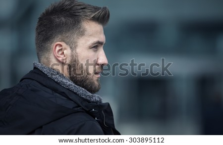 Portrait from an attractive man with a beard - stock photo