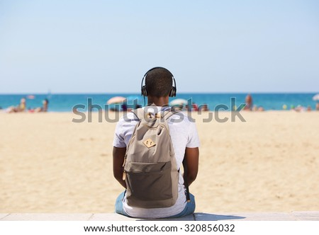 Portrait from behind of a young man sitting by the beach listening to music on headphones - stock photo