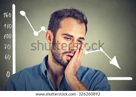 Portrait frustrated stressed young man desperate with financial market chart graphic going down on grey office wall background. Poor economy financial crisis concept. Face expression, emotion  - stock photo