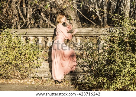 Portrait full length of Beautiful young adult slim caucasian woman stand against abandoned old fence. Redhead cute girl wear long fashion dress. Empty Copy space for inscription - stock photo