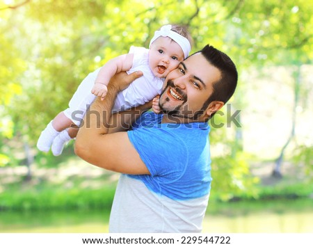Portrait funny positive father and baby having fun outdoors in summer day